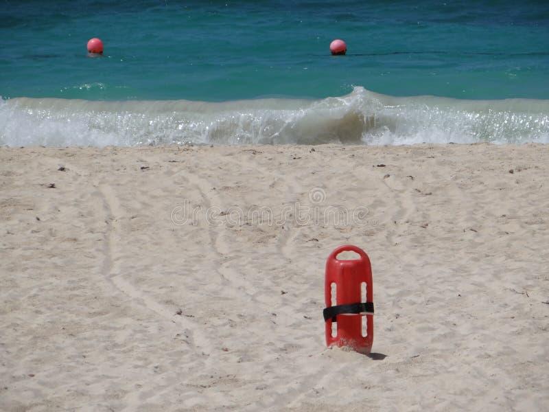 Salvavidas rojo de la salvación en arena en la playa imágenes de archivo libres de regalías