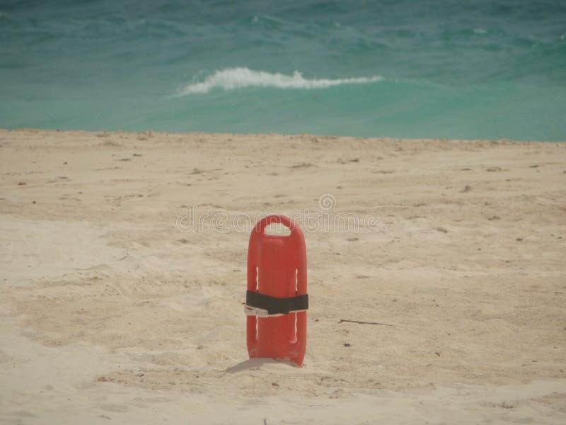 Salvavidas rojo de la salvación en arena en la playa imagen de archivo libre de regalías