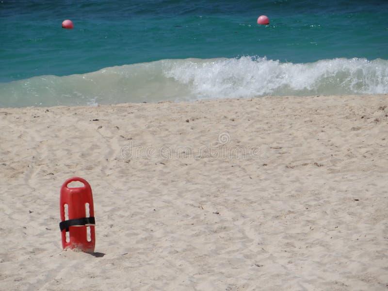 Salvavidas rojo de la salvación en arena en la playa fotografía de archivo