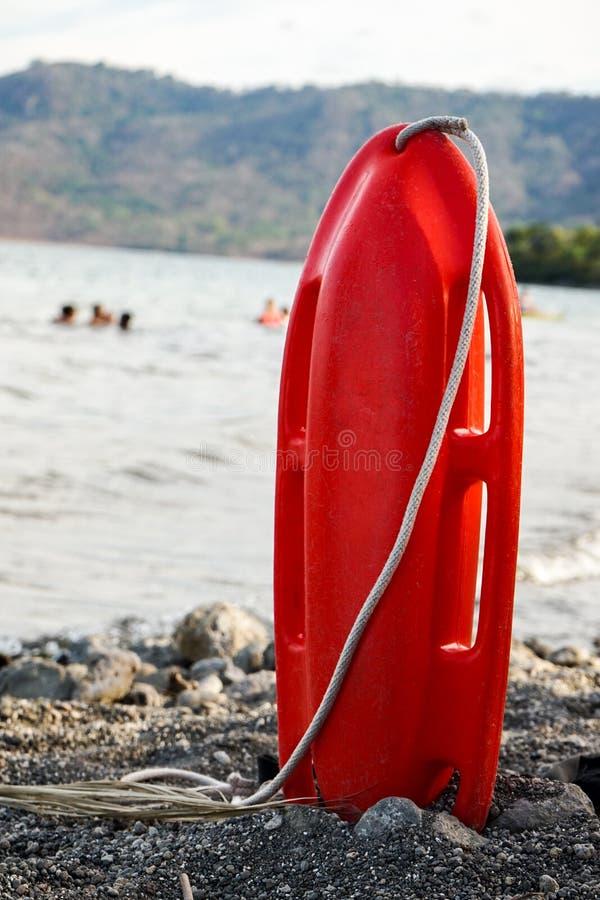 Salvavidas rojo de la salvaci?n en arena en la playa foto de archivo