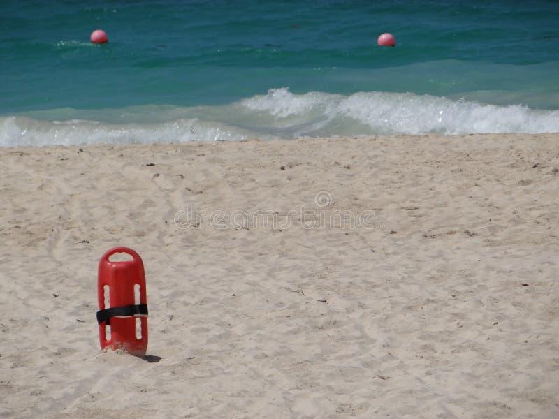 Salvavidas rojo del fLifesaver en arena en la playa imagen de archivo