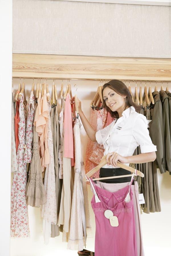 Salve la ropa de trabajo y colgante del ayudante en tienda imagen de archivo libre de regalías