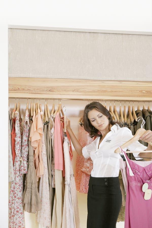 Salve la ropa de trabajo y colgante del ayudante en tienda imagenes de archivo