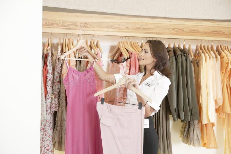 Salve la ropa de trabajo y colgante del ayudante en tienda fotografía de archivo