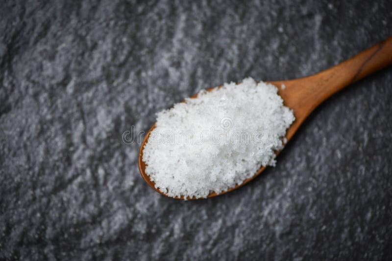 Salz im hölzernen Löffel der dunkle Hintergrund stockfotos