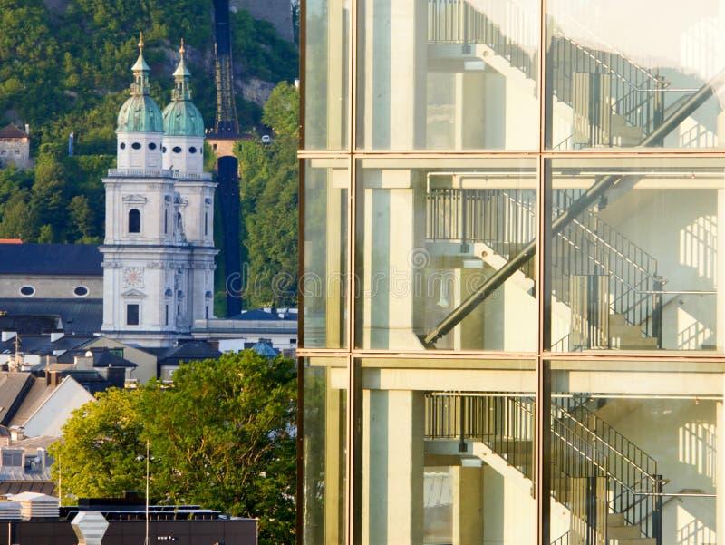 Salzburg/Österreich - 2. Juni 2019: Architekturkontrast mit alten Kirchtürmen und einem modernen Gebäude lizenzfreie stockfotos