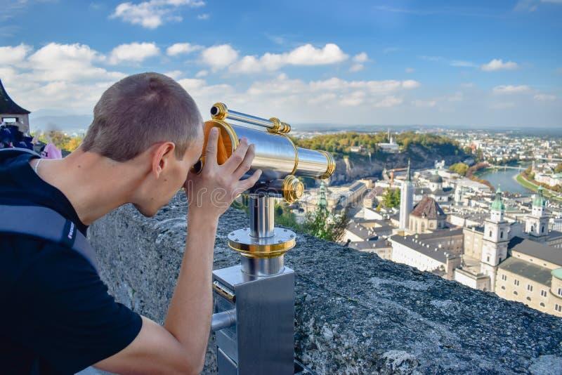 SALZBURG, ÖSTERREICH - OKTOBER 10, 2018: Junger Mann betrachtet durch Teleskop alter Stadt in Salzburg Österreich stockbild