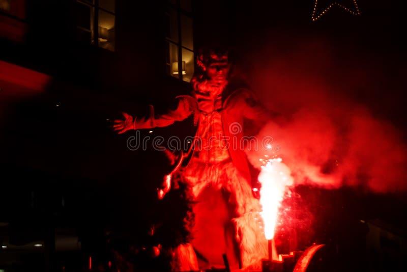 Salzburg, Austria: December 3 2014: Krampus with fire and smoke standing on a coach during Krampuslauf in Getreidegasse Salzburg stock image