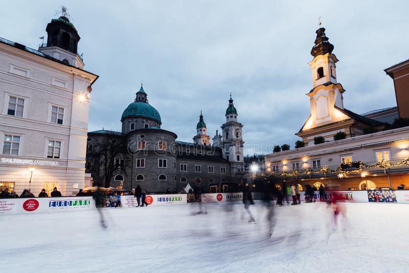 SALZBURG, AUSTRIA - DECEMBER 2018: people skating on the ice rink at old town Christmas market royalty free stock image