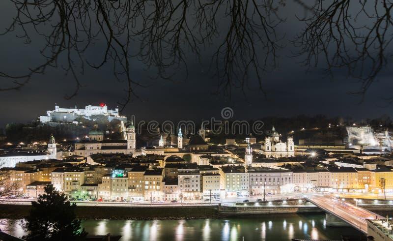 SALZBURG, AUSTRIA - ENERO DE 2019: vista nocturna sobre la ciudad vieja enmarcada con las ramas de árbol foto de archivo libre de regalías