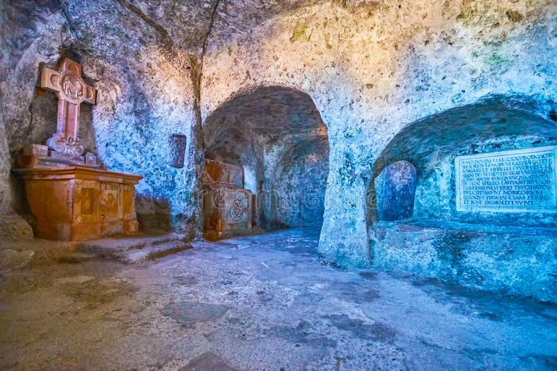 The hewn chapel in catacombs of Salzburg, Austria. SALZBURG, AUSTRIA - FEBRUARY 27, 2019: The hewn chapel with large stone carved cross in catacombs of St Peter royalty free stock photos