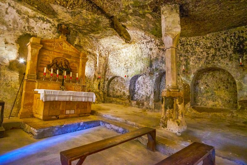 The cave chapel in catacombs of Salzburg, Austria. SALZBURG, AUSTRIA - FEBRUARY 27, 2019: The small medieval cave chapel in catacombs of St Peter cemetery with stock images
