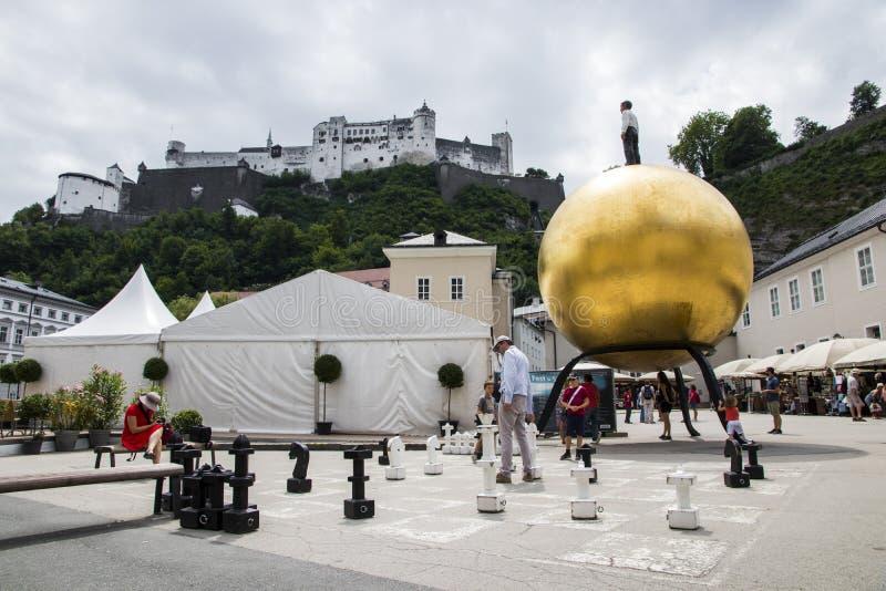 Salzburg, Austria. The Sphaera sculpture in Kapitelplatz, Salzburg, Austria, with a man standing over a golden Mozart ball Mozartkugel and a chessboard stock photo