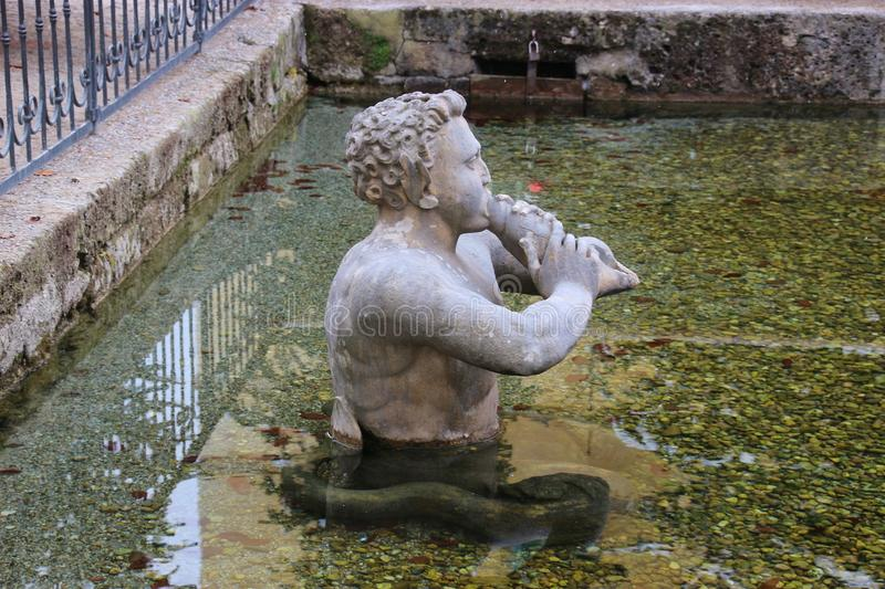 Stone sculpture of a Triton blowing on his conch shell trumpet. Salzburg, Austria. Salzburg, Austria: Stone sculpture of a Triton, a greek merman, blowing on stock photo