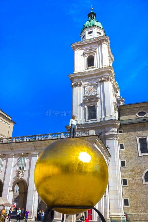Salzburg, Oostenrijk - Mei 01, 2017: Het gouden balstandbeeld met een mens op het hoogste beeldhouwwerk, Kapitelplatz-Vierkant, S stock foto