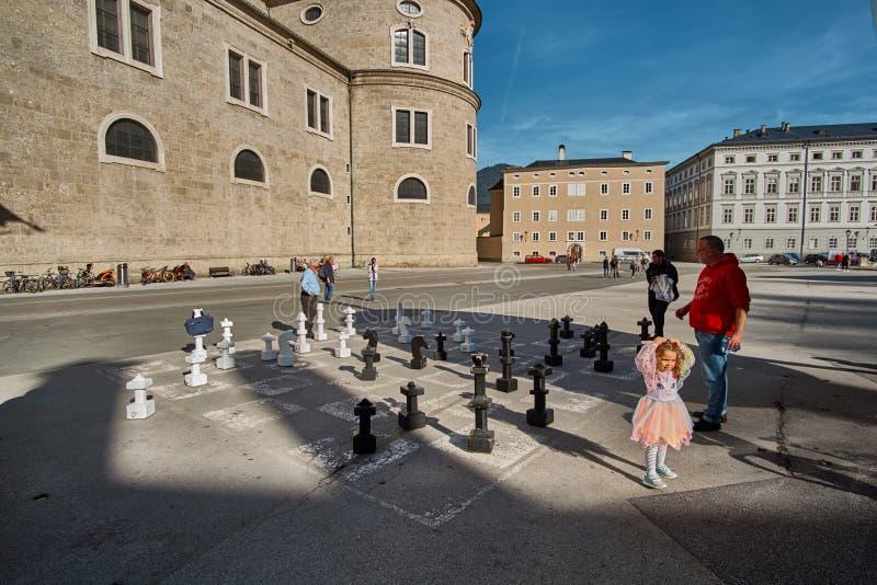 Salzburg, Salzburger Land, Austria - September 11, 2018: Man with a little girl playing huge chess at Kapitelplatz Chapter Square royalty free stock photography
