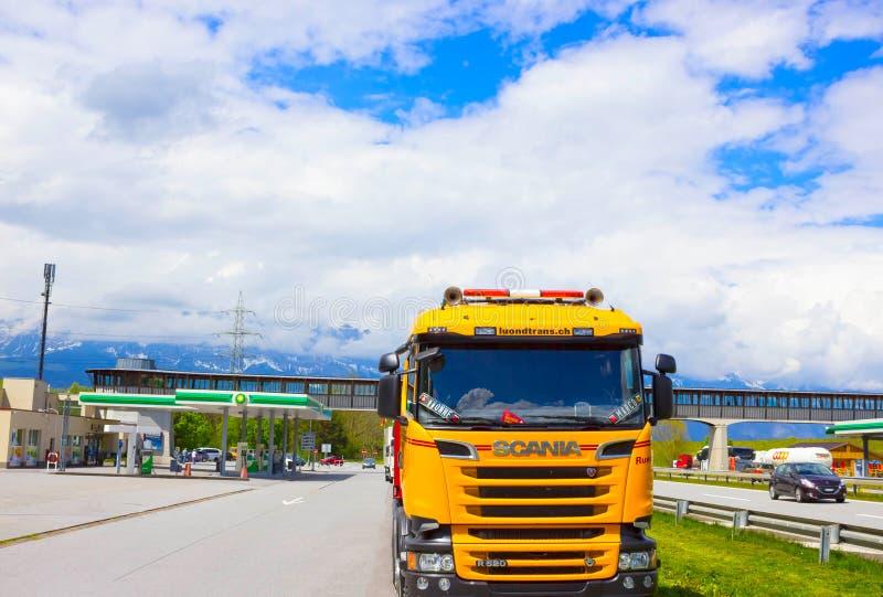 Salzburgerland, Oostenrijk - MEI 3, 2017: De gele Scania-vrachtwagen wordt geparkeerd dichtbij het benzinestation stock afbeelding