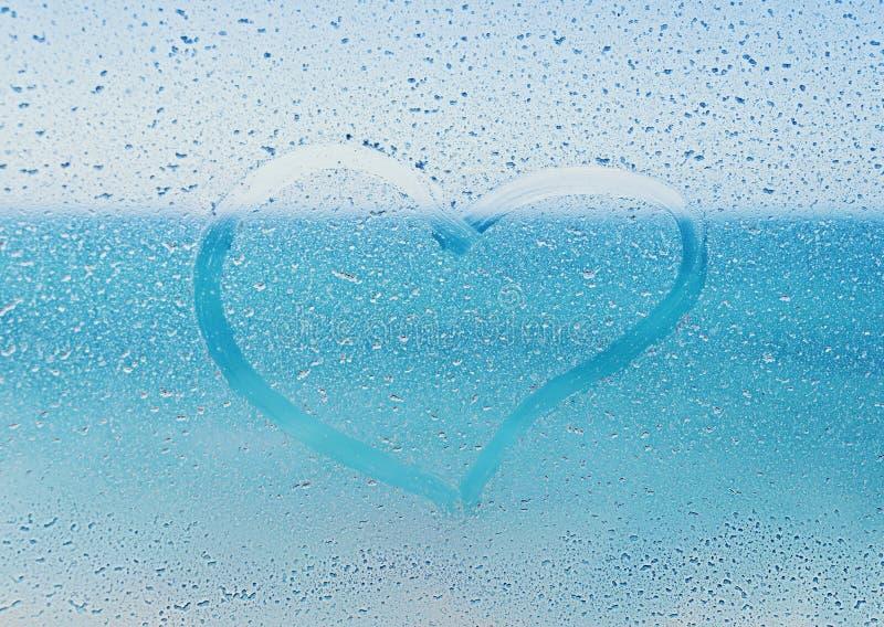 Salzen Sie das Herz, das auf dem Fensterglas mit Blick auf den Ozean gemalt wird lizenzfreie stockfotos