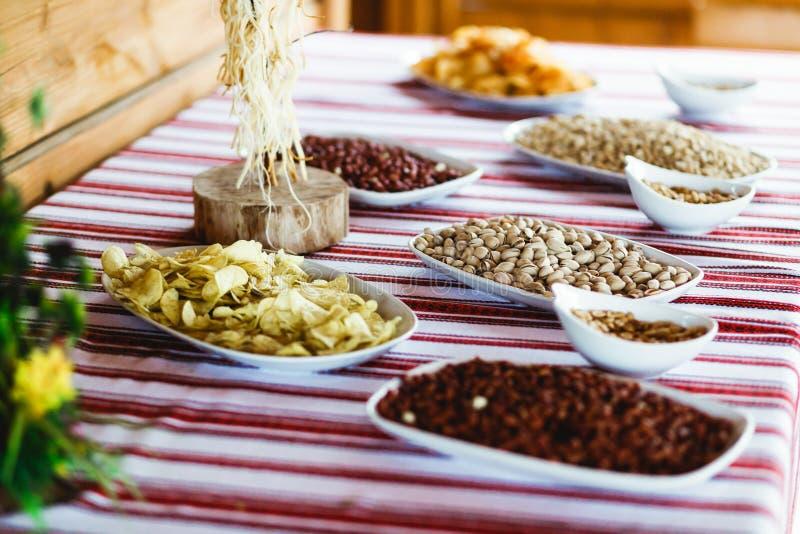 Salzige Aperitifs liegen auf dem Tisch bedeckt mit ethnischem Stoff stockfotos