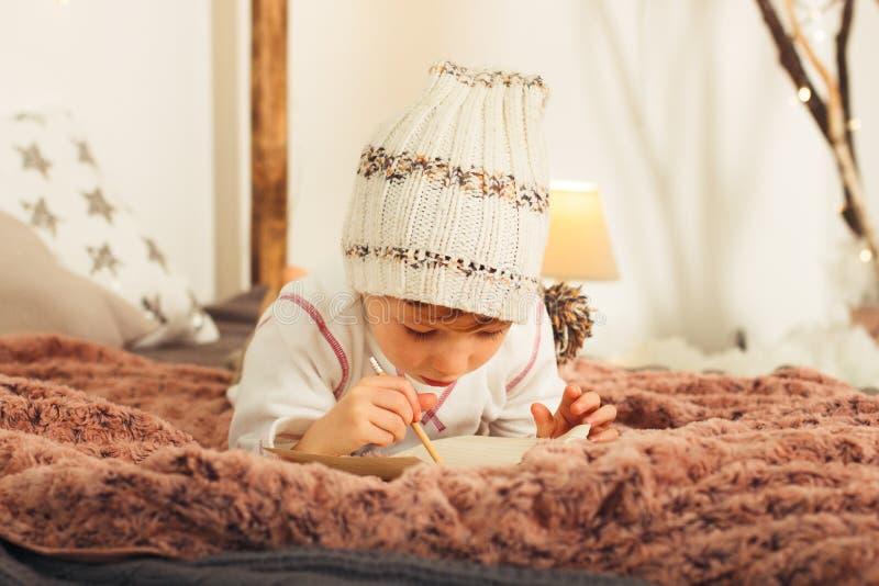 Samall skrivar den gulliga blonda pojken brevet till Santa Claus på sängen arkivfoto