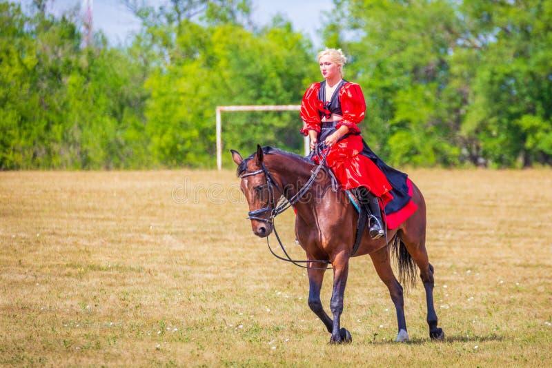 Samara, agosto 2018: Dressage di sport equestre, passaggio - una ragazza in un bello vestito si siede su un cavallo fotografia stock libera da diritti