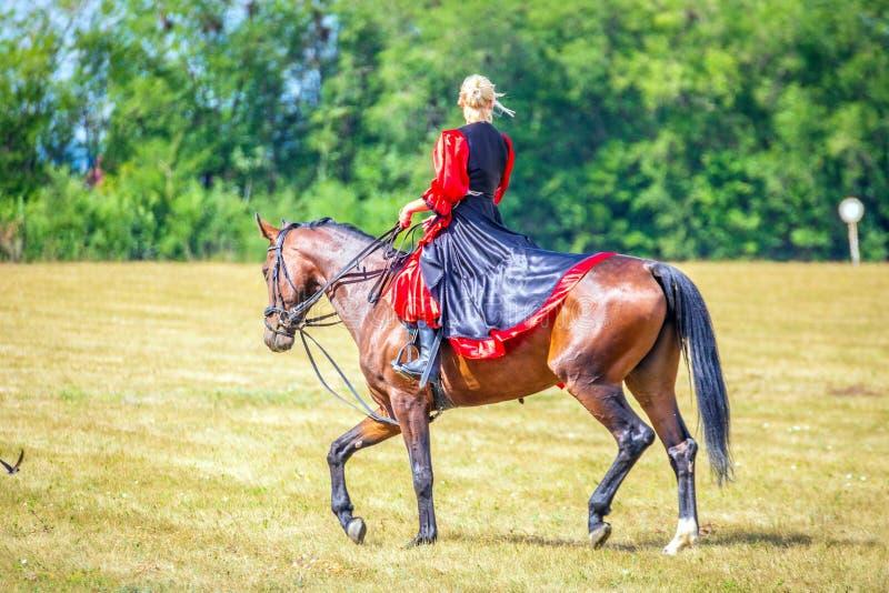 Samara, Augustus 2018: Ruitersportdressuur, passage - een jong meisje in een mooie kleding zit op een paard royalty-vrije stock afbeeldingen