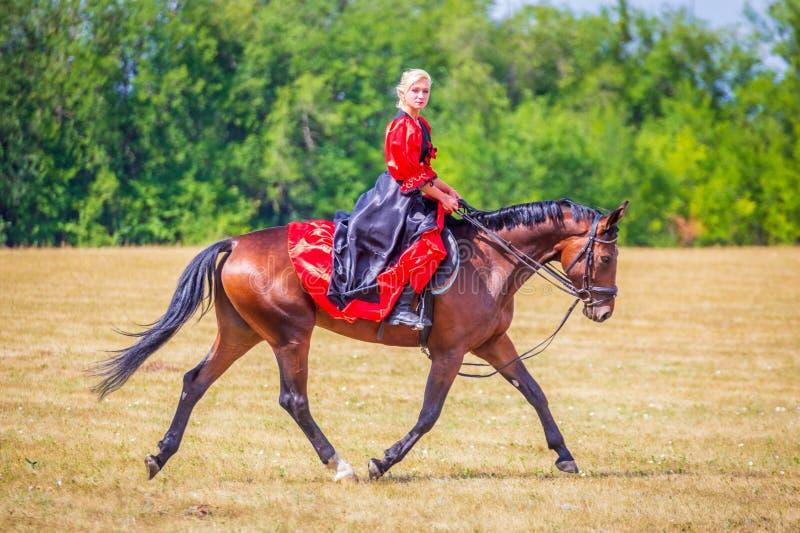 Samara, Augustus 2018: Ruitersportdressuur, passage - een jong meisje in een mooie kleding zit op een paard stock foto's
