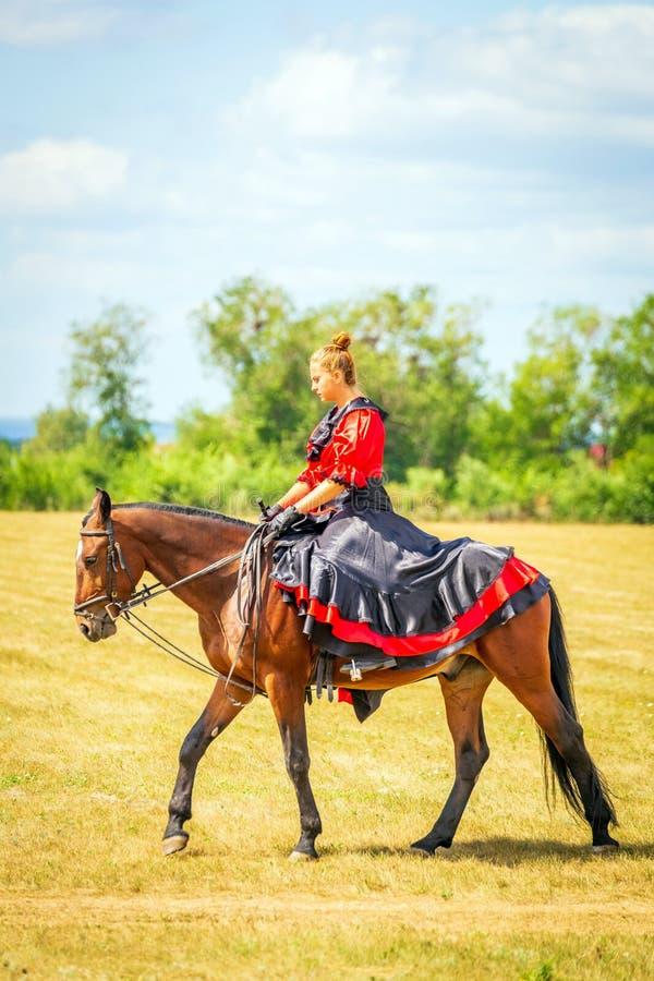 Samara, Augustus 2018: Ruitersportdressuur, passage - een jong meisje in een mooie kleding zit op een paard royalty-vrije stock foto