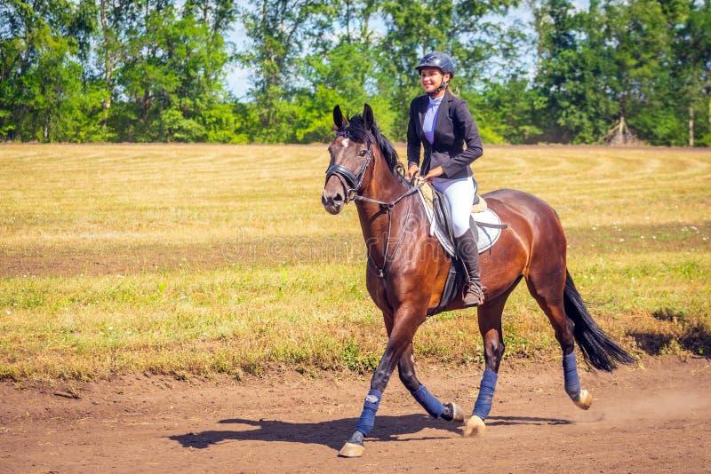 Samara, Augustus 2018: Ruitersportdressuur, passage - een jong meisje in een mooie kleding zit op een paard royalty-vrije stock fotografie