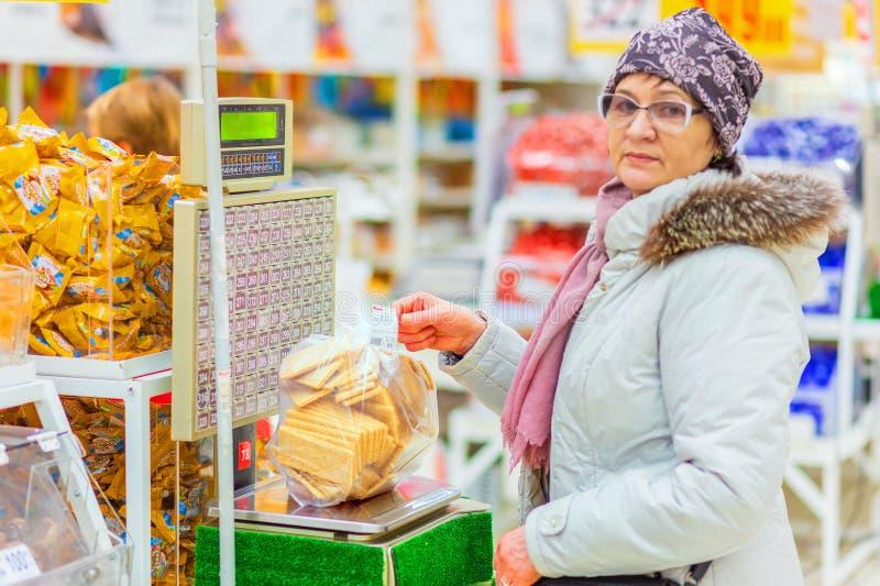 Samara, em janeiro de 2019: Uma mulher madura bonita pesa os produtos na loja do autosserviço fotos de stock royalty free