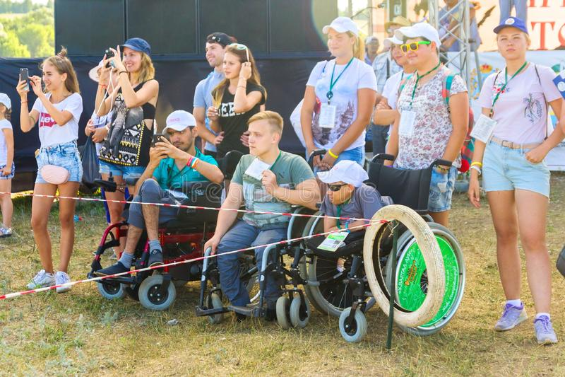 Samara, em julho de 2018: Usuários de cadeira de rodas com os voluntários no festival imagens de stock royalty free