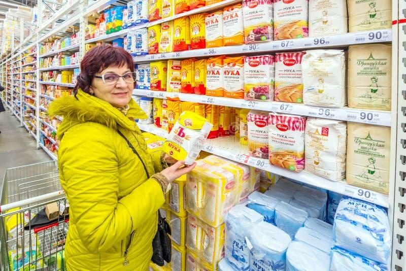 Samara March 2019: as mulheres maduras bonitas escolhem a farinha em um supermercado fotografia de stock