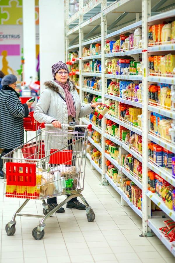 Samara, Styczeń 2019: Piękna dojrzała kobieta wybiera produkty w samoobsługowym sklepie obraz stock