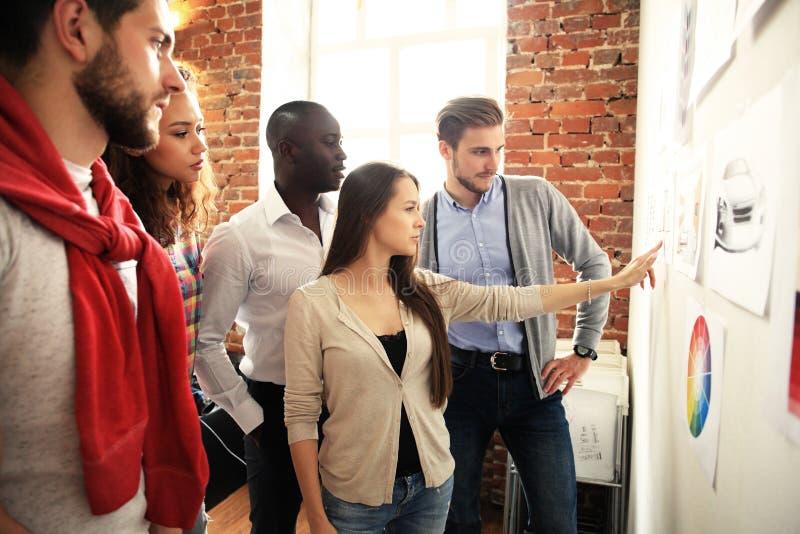 Samarbete är en tangent till bästa resultat Grupp av ungt modernt folk i smart för planläggningsaffär för tillfälliga kläder stra arkivbild