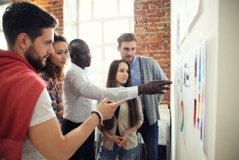Samarbete är en tangent till bästa resultat Grupp av ungt modernt folk i smart för planläggningsaffär för tillfälliga kläder stra royaltyfri fotografi