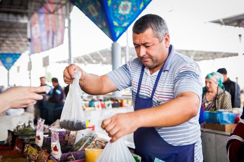 Salesman packing spices that he just sold to a customer at main city market bazaar stock images