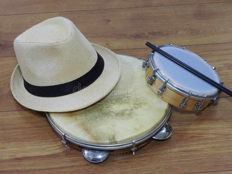 A samba player sambista hat and two Brazilian percussion musical instruments: pandeiro tambourine and tamborim with drumstick. stock images