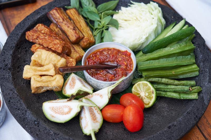 Sambal Dan lalapan: eine Vielzahl des indonesischen Sambals mit Kopfsalat und Gurke als Salat lizenzfreies stockfoto