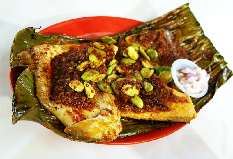 Sambal Stingray. BBQ stingray on banana leaf garnished with spring onions, onions, red chillies paste and lime on a plate stock image