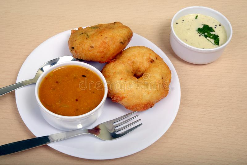 Sambar vada and coconut chutney a South Indian food, on wooden background. Sambhar vada is also known as Medu vada, a very popular food not only in South India stock photography