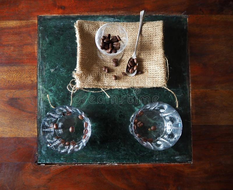 sambuca,意大利利口酒两块玻璃,用说谎在一张木桌上的绿色大理石表面上的咖啡豆 免版税图库摄影