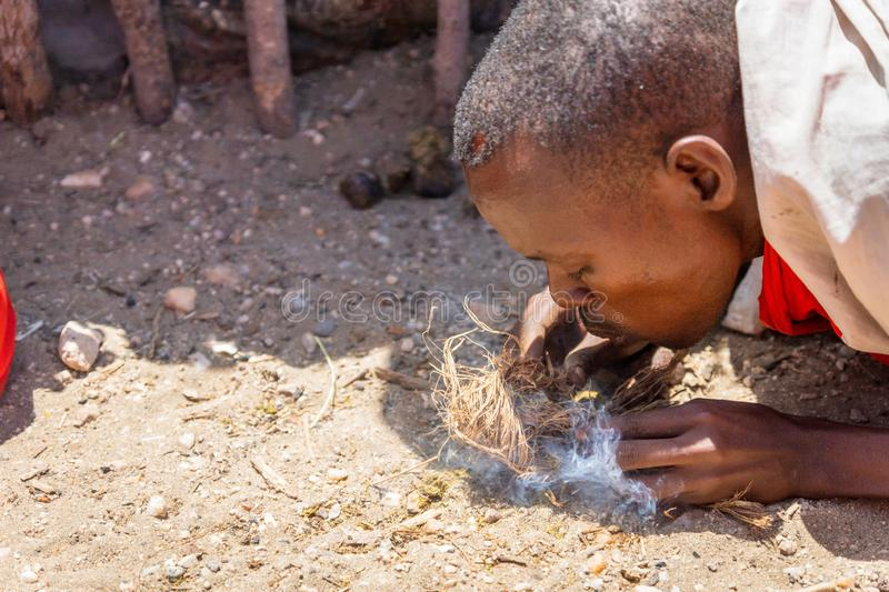 Masai warrior are making a fire with dry grass on the ground royalty free stock image