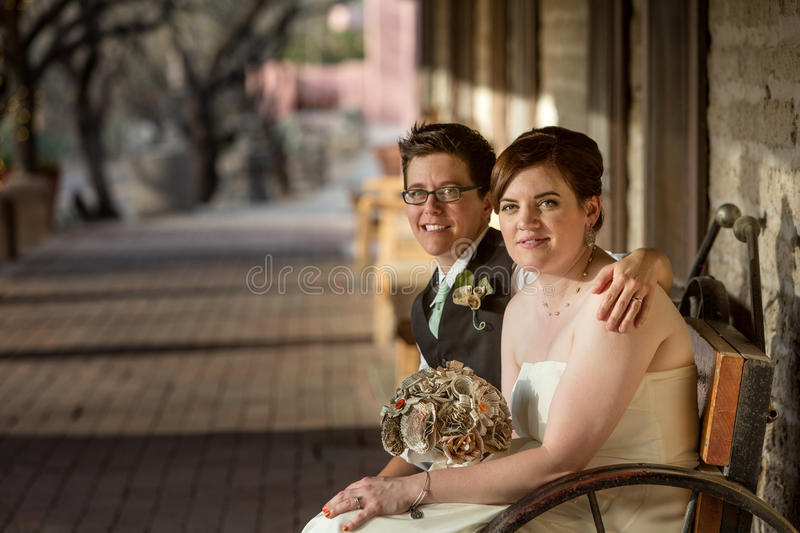Same Sex Bride and Groom. Smiling same sex bride and groom seated together royalty free stock photo