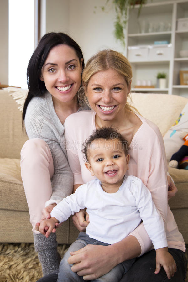 Same sex couple with baby son. Female couple sit together with their son in their home and all smile for the camera royalty free stock photography