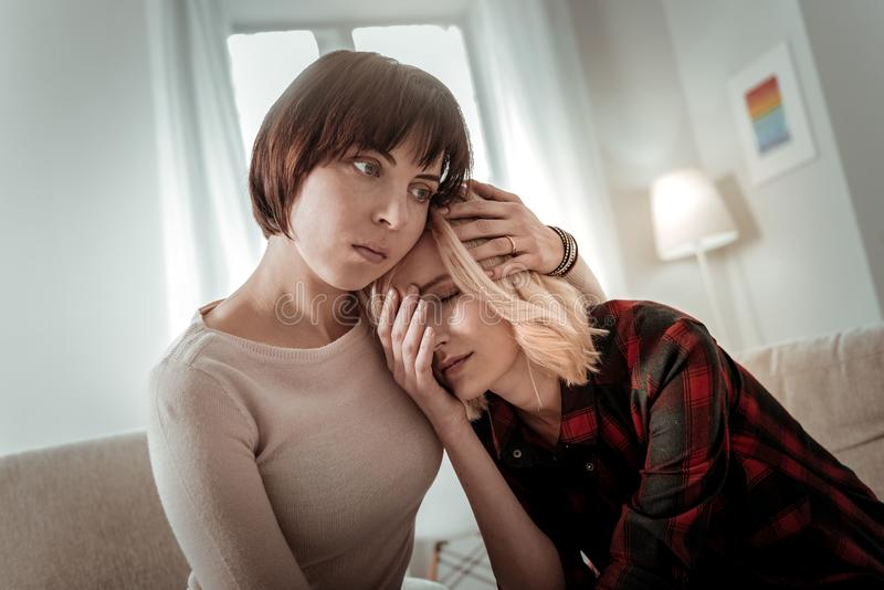 Same sex couple being overwhelmed with grief. Woman calming down. Same sex couple being overwhelmed with grief and supporting each other stock image