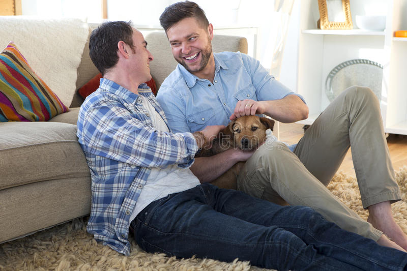 Same sex couple at home with dog royalty free stock image