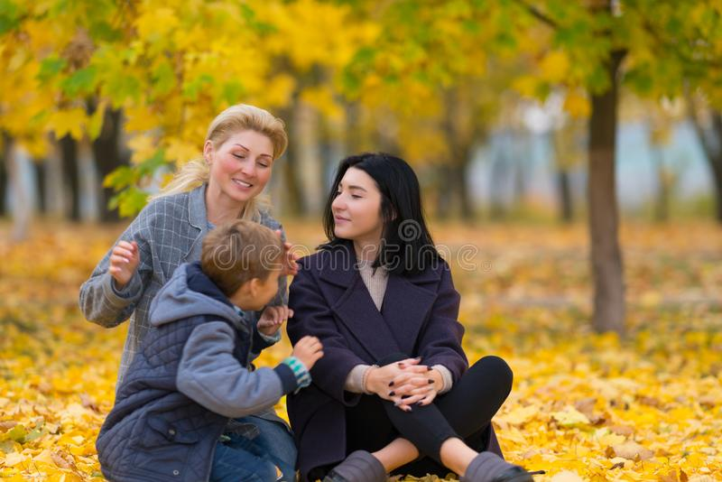 Same sex female couple with son in autumn park. royalty free stock image