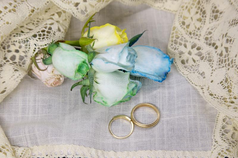 Same sex marriage. Mens gold wedding bands on white linen and lace with rainbow roases as metaphor for same sex weddincg ceremony with copy space stock photography
