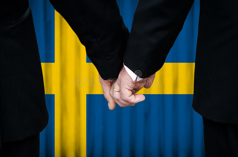 Same-Sex Marriage in Sweden. Two gay men stand hand in hand before a marriage altar featuring an overlay of the flag colors of Sweden, having just been legally stock photos