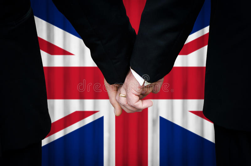 Same-Sex Marriage in United Kingdom. Two gay men stand hand in hand before a marriage altar featuring an overlay of the Union Flag, having just been married stock image